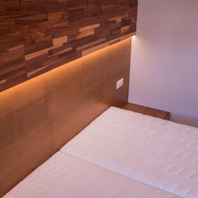 Realizácia dreveného interiériu spálne s dreveným obkladom steny.